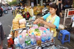 Marchande de pad thaï (nouilles sautées aux légumes et aux oeufs, auxquelles on peut ajouter du poulet, des crevettes...)