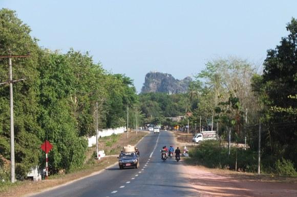 On the road again ! A l'horizon, Kyauktalon Taung, pic karstique surmonté de pagodes