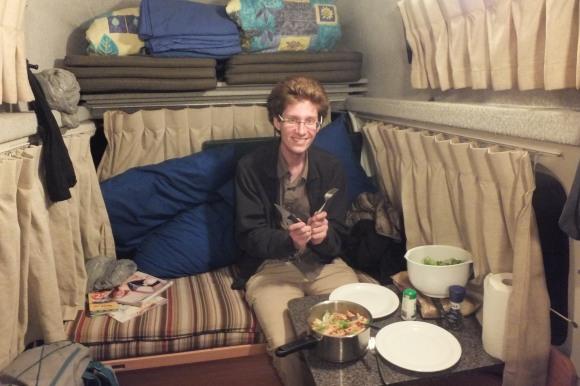 Premier dîner dans notre petit van ! Benoît est assis sur la banquette qui se transforme en lit pour la nuit...